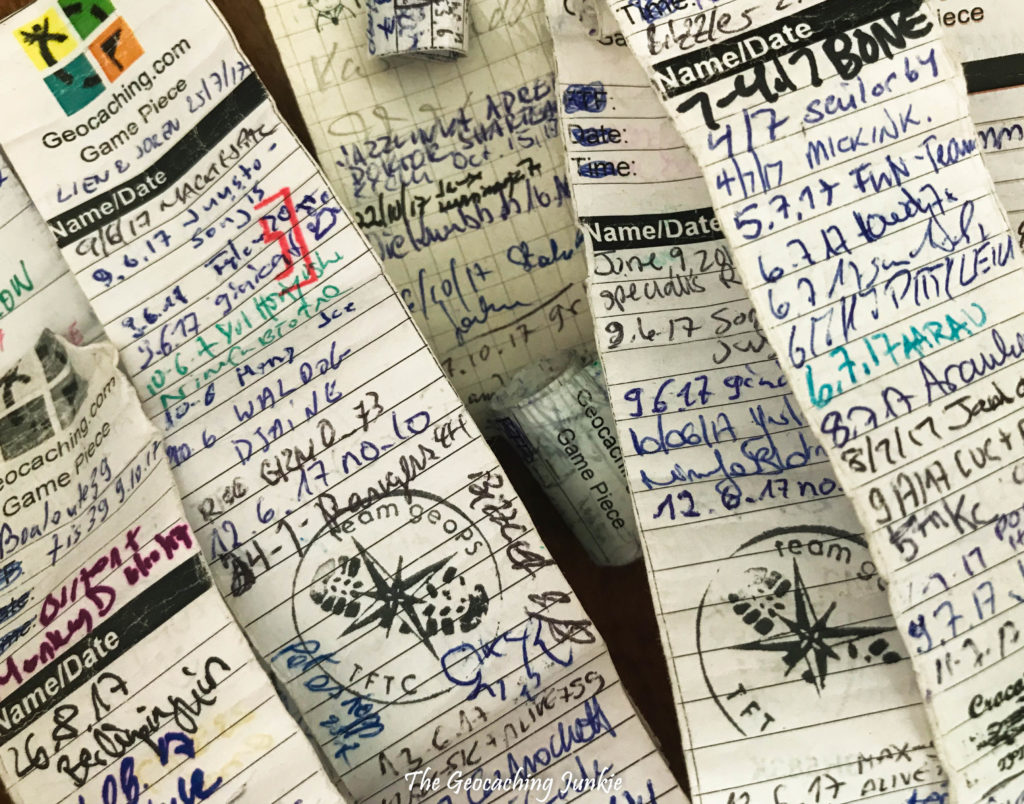 Several geocaching logbooks stacked haphazardly on top of one another