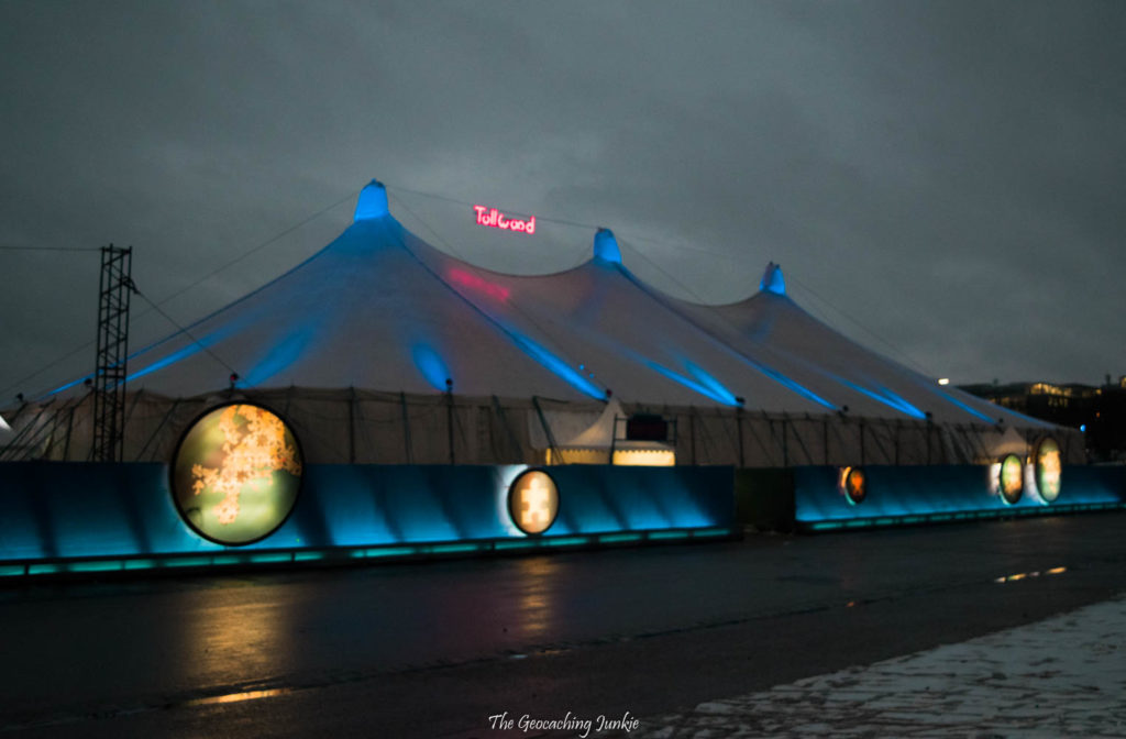 A large circus style tent is illuminated with blue lights at Winter Tollwood in Munich, Germany